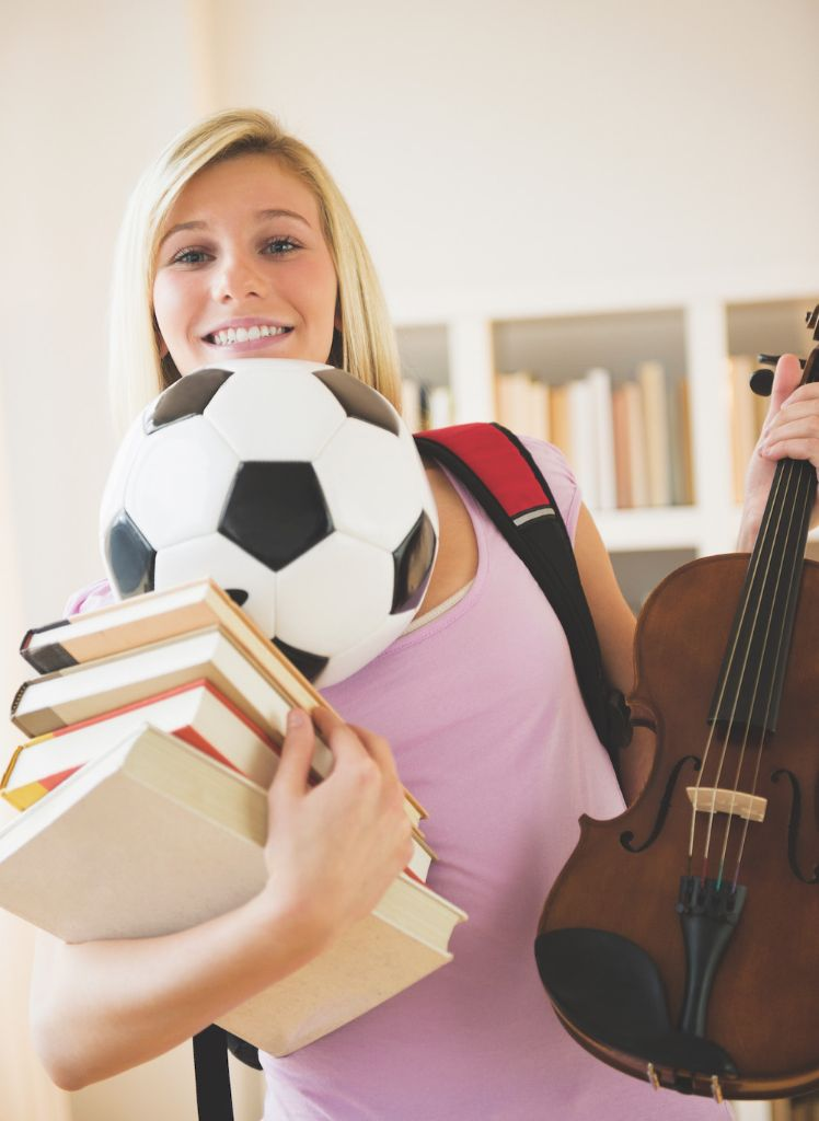 Teen balancing books, soccer ball and violin